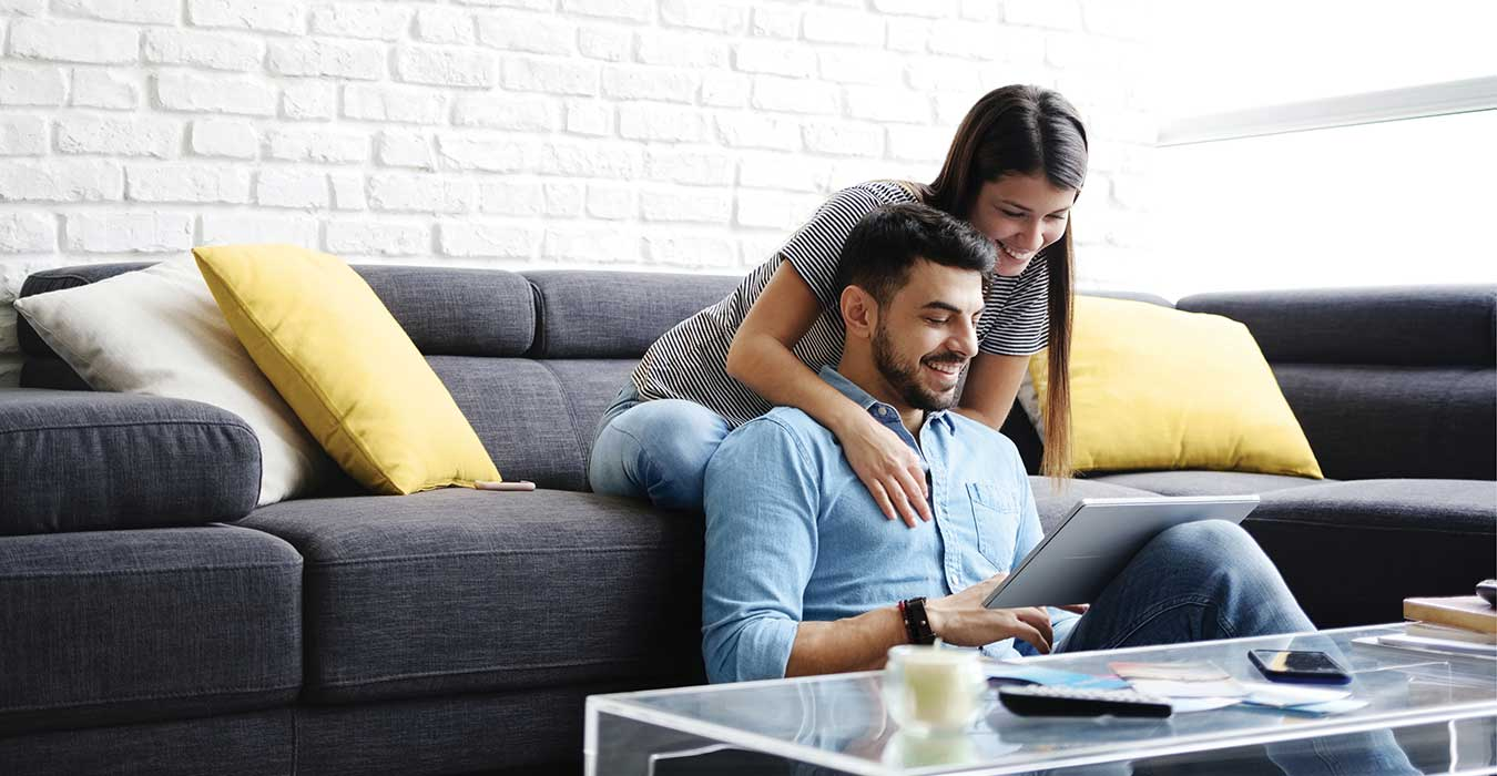 Couple on a sofa looking at an online application.